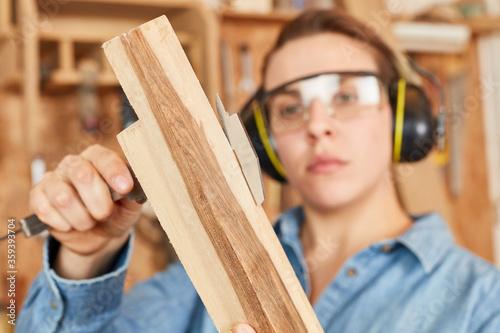Woman as a carpenter apprentice with vernier caliper Wallpaper Mural