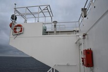 Bridge Wing Of The Merchant Container Vessel With Panama Shelter Construction Gyro Compass Repeater,  Red Color Lifesaving Ring, Fire Box And Light Green Maneuvering Remote Control Station