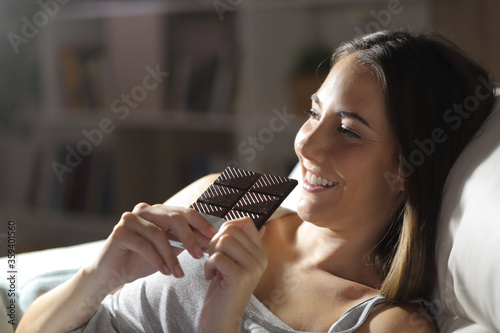 Happy girl eating chocolate bar at night Canvas-taulu