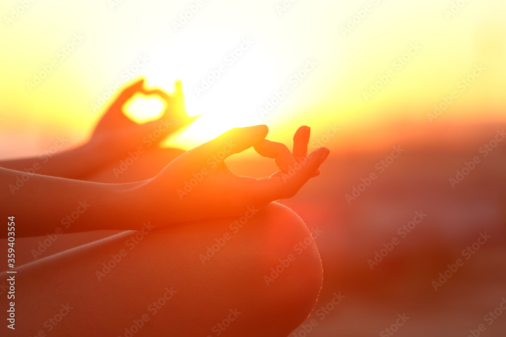 Fototapeta Woman hands doing yoga relaxing at sunset outdoor