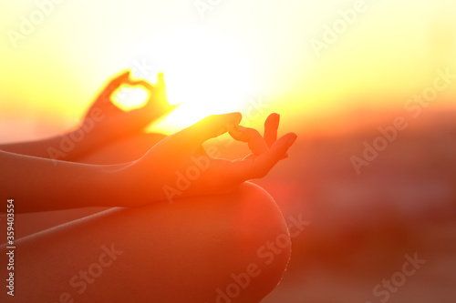 Woman hands doing yoga relaxing at sunset outdoor - 359403554