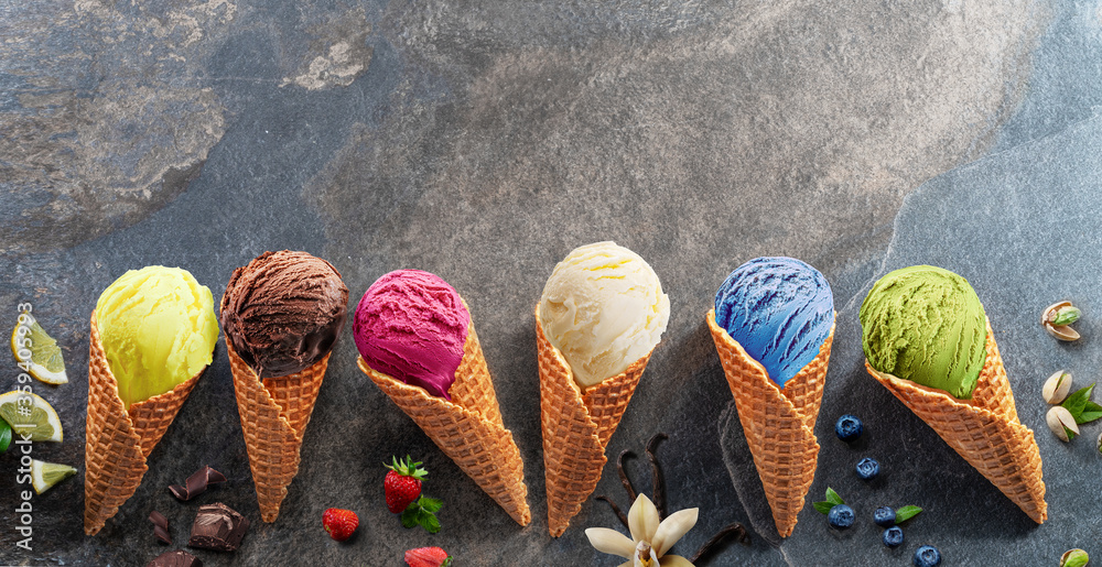 Fototapeta Set of various colorful ice creams in waffle cones with fruits slices on the grey background.