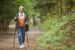 Full length portrait of active senior woman walking towards camera with Nordic poles while enjoying hike in beautiful autumn forest, copy space