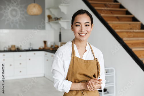 Smiling attractive young asian woman wearing apron Canvas Print