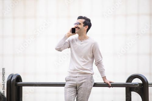 Joven trabajador con bigote y gafas sonriente mirando el teléfono móvil Canvas Print