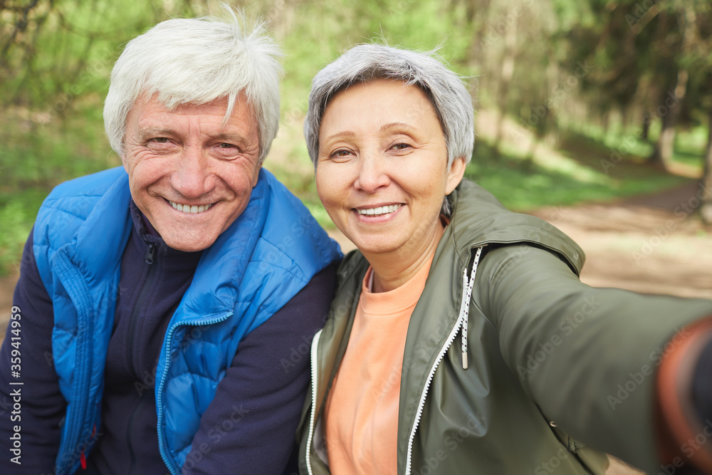 Fototapeta POV portrait of active senior couple looking at camera and smiling while taking selfie photo during hike in autumn forest, copy space