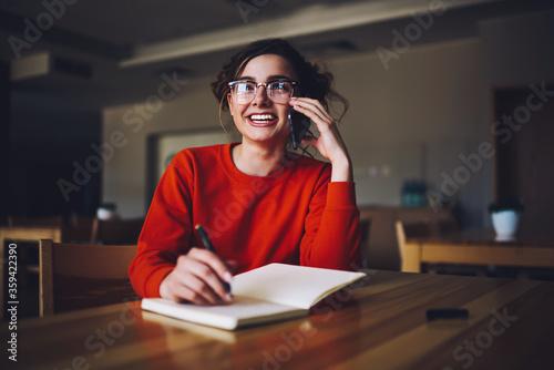 Charming funny female students in trendy eyewear having friendly phone conversat Wallpaper Mural