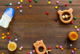 Baby accessories and toys on wooden table top-down copy space