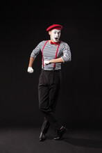 A Male Mime Artist Performing, Isolated On Black Background