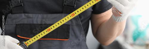 Stampa su Tela Repairman in uniform gloves measures tape measure
