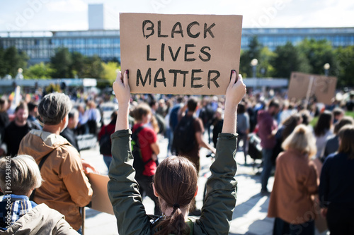Fototapety, obrazy: Rear view of black lives matters protesters holding signs and marching outdoors in streets.