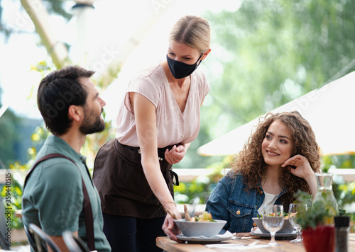 Waitress with face mask serving happy couple outdoors on terrace restaurant. - 359440515