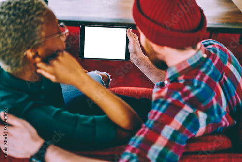 Fotografiet Cropped back view of diverse marriage discussing media on modern tablet with copy space display for internet content