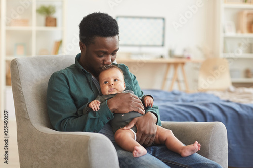 Obraz Portrait of caring African-American man holding cute mixed-race baby while sitting in comfortable armchair at home, copy space - fototapety do salonu