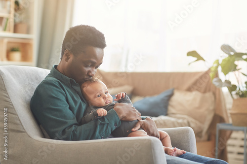 Leinwand Poster Side view portrait of caring African-American man holding cute mixed-race baby w