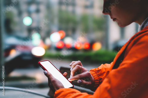 Cropped image of female person in bright orange jacket using modern mobile phone device with touch copy space screen outdoors on city bokeh lights background. Woman typing text message on smartphone