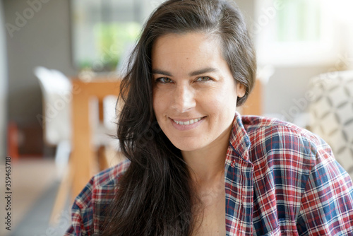 Fototapeta Portrait of beautiful and smiling dark-haired woman relaxing at home