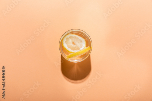 top view of fresh water with lemon slices in glass on beige with shadow