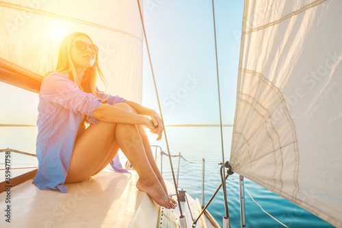 Fototapeta Young happy woman enjoying sunset from deck of sailing boat moving in sea at evening time