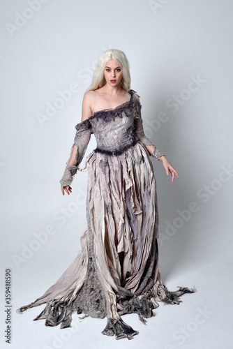 full length portrait of blonde girl wearing long torn, old wedding gown. standing pose on a studio background.