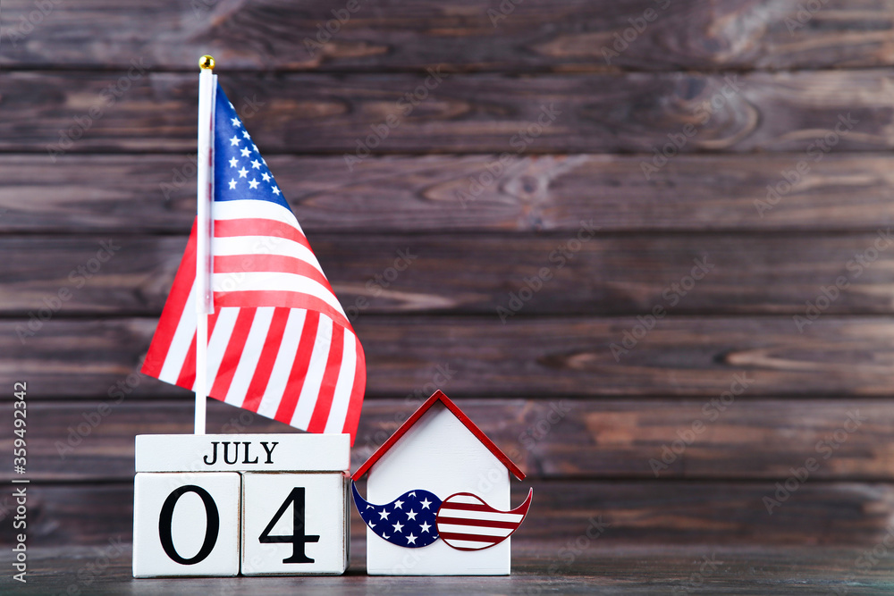 Fototapeta Independence Day concept. American flag with house model and cube calendar on wooden background