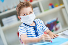 Adorable Little Boy In Kindergarten With Mask On Due To Coronavirus Pandemic
