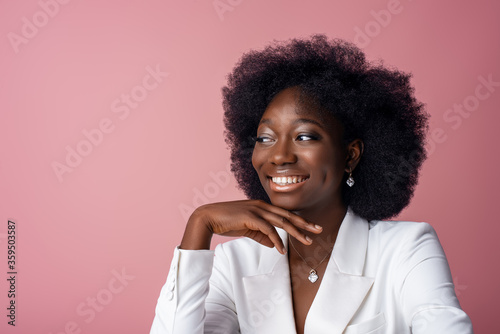 Fotografía Yong beautiful happy smiling African American woman, model wearing elegant jewelry, white blazer, looking aside, posing in studio, on pink background