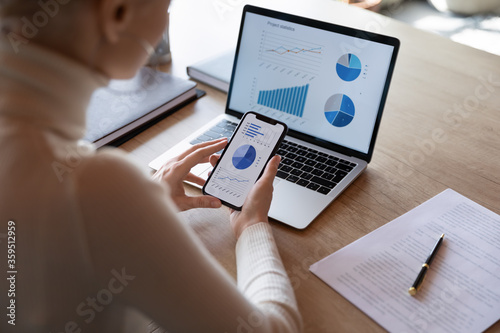 Fototapeta Woman hold smartphone use pc at workplace. Project stats financial data sales charts on laptop and cellphone screen, close up view over shoulder. Report preparation, synchronization for safety concept obraz