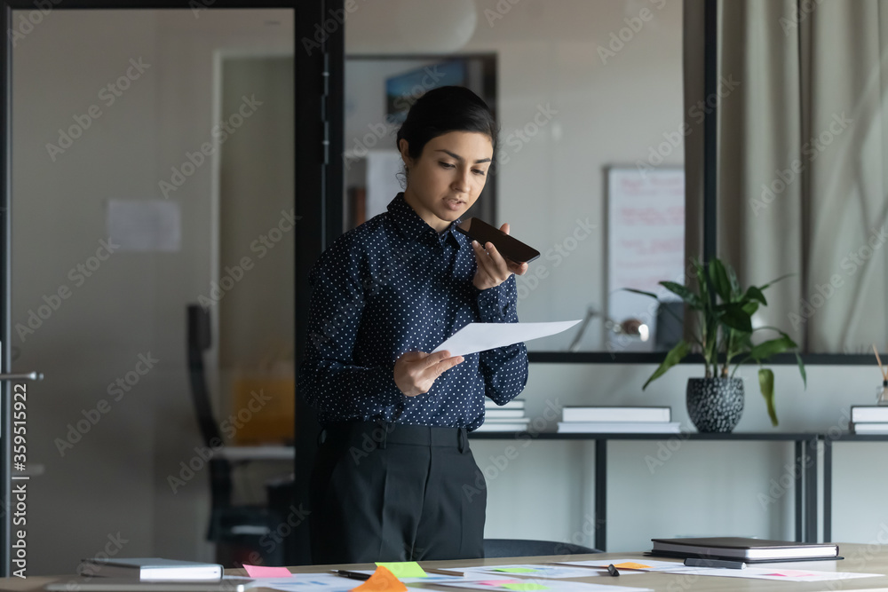 Fototapeta Serious focused indian project manager hold smartphone talking discuss working moments use loudspeaker read formal letter consults with boss distantly, do financial report research at boardroom alone