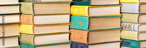 A stack of hardback books on a table in a library. Fototapet