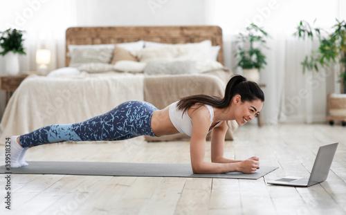 Fototapeta Home Exercises. Sporty asian girl doing yoga plank in front of laptop obraz