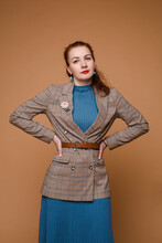 Stock Studio Portrait Of An Elegant Woman With Red Hair Wearing Blue Knitwear Dress And Checked Jacket With Brown Belt And Brooch In Shape Of Rose With Her Arms On Waist..