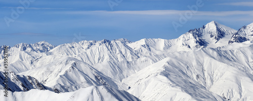Panoramic view on high snowy mountains and blue sky with clouds #359521116