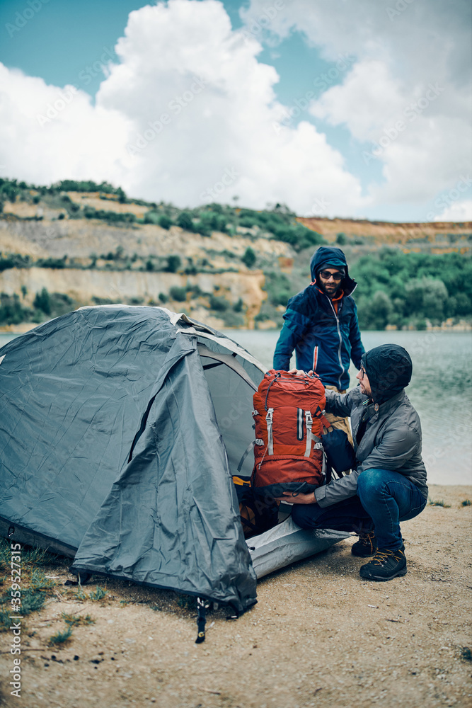Fototapeta Two men on camping trip putting backpacks into tent by the lake on rainy and cold weather.