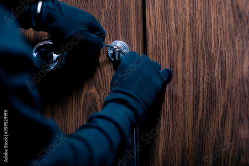 Robber in black mask cracking door with metal picklock Canvas Print