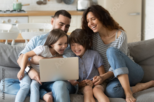 Close up happy parents with daughter and son using laptop sitting on couch at home. Smiling mother, father and cute children looking at laptop screen using video call. Family having fun with computer. - 359531187