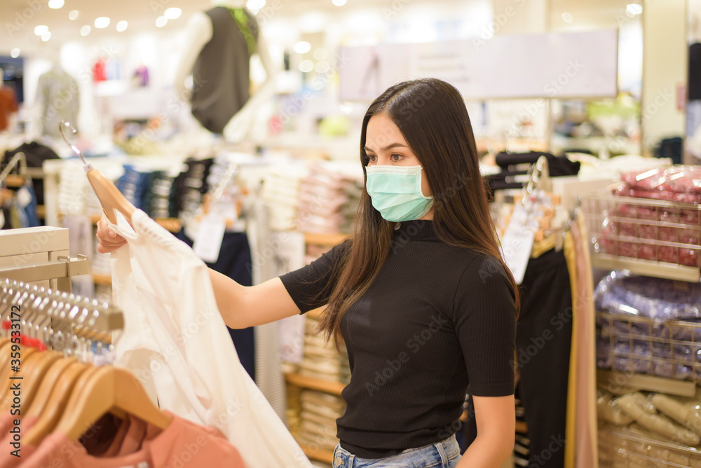 Fototapeta woman with face mask is shopping clothes in Shopping center
