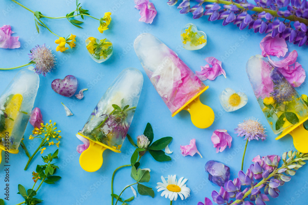 Fototapeta Floral Ice Pops. Frozen popsicles and ice cubes made of colorful wildflowers on blue background flat lay with fresh summer flowers. Hello summer concept. Refreshing vegan sweets