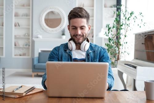 Obraz Handsome modern man designer working on laptop online, using internet at home - fototapety do salonu