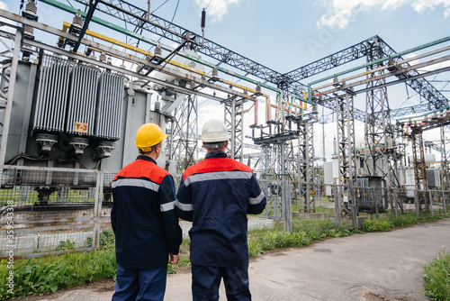 Photo Two specialist electrical substation engineers inspect modern high-voltage equipment
