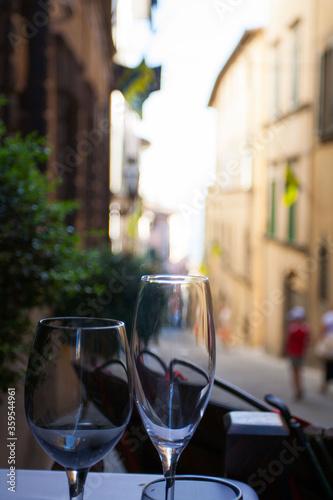 Stolik z kieliszkami wina - uliczka w Cortona, Toskania, Włochy