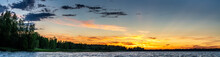 Panorama Of Scandinavian White Night At Polar And Subpolar Area In Sweden. Midnight Sun Just Below Horizon Line, Sun Rays Illuminate Highest Clouds In Atmosphere. Lake And Forest At Coast Line