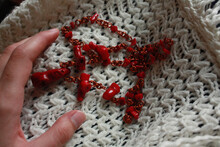 Red Beads Made Of Natural Coral And Copper Wire And Female Hand On A White Background.