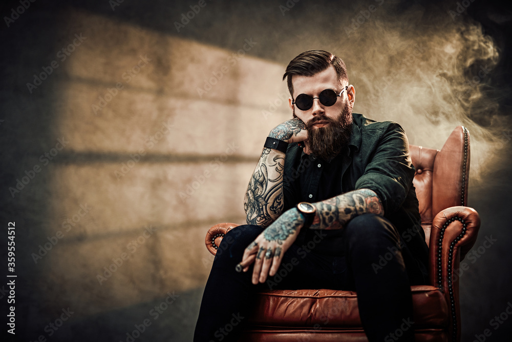 Fototapeta Cool bearded young man sitting on a vintage chair in a dark studio with smoke and window silhouette in the background