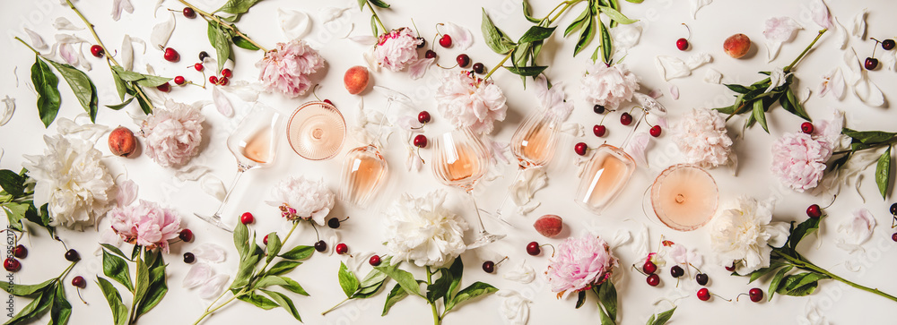 Fototapeta Rose wine variety layout. Flat-lay of rose wine in various glasses with flowers and summer fruit over plain white background, top view. Summer drink for party, wine shop or wine tasting concept