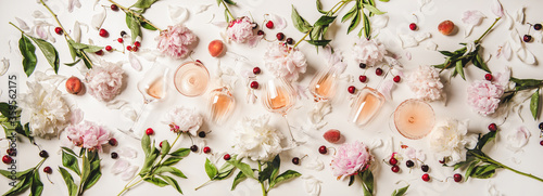 Rose wine variety layout. Flat-lay of rose wine in various glasses with flowers and summer fruit over plain white background, top view. Summer drink for party, wine shop or wine tasting concept