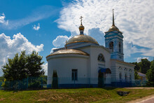 White-stone Orthodox Church With A Blue Roof And Golden Domes Surrounded By A Blue Iron Fence
