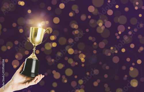 Fotografía Woman holding gold trophy cup on violet background, closeup
