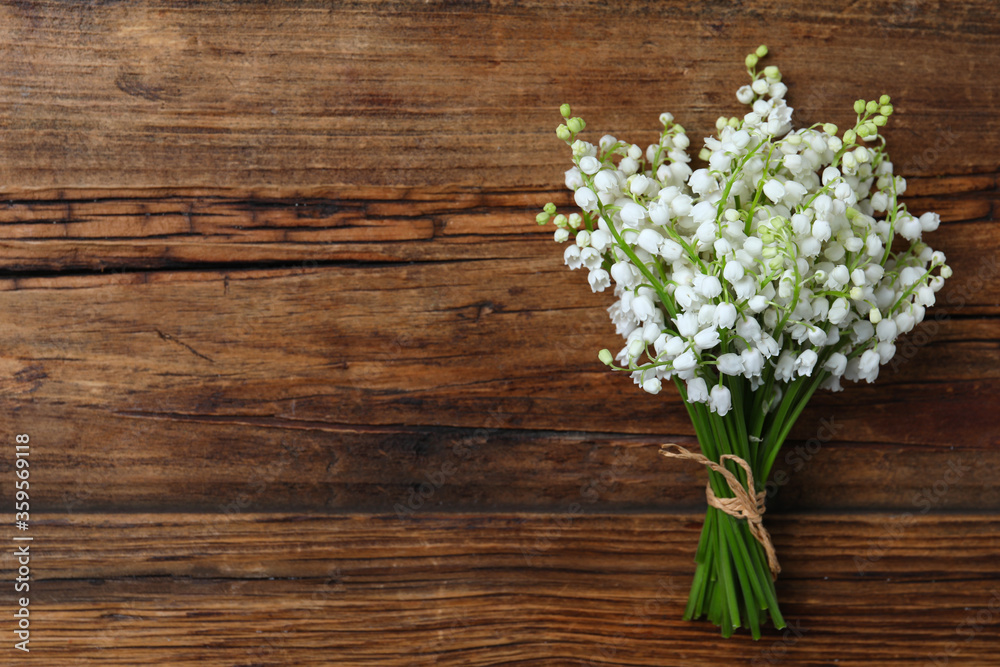 Fototapeta Beautiful lily of the valley flowers on wooden table, top view. Space for text