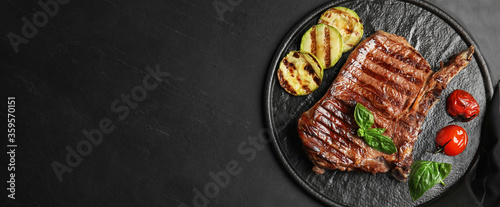 Slate plate with grilled meat steak and space for text on black table, top view. Banner design